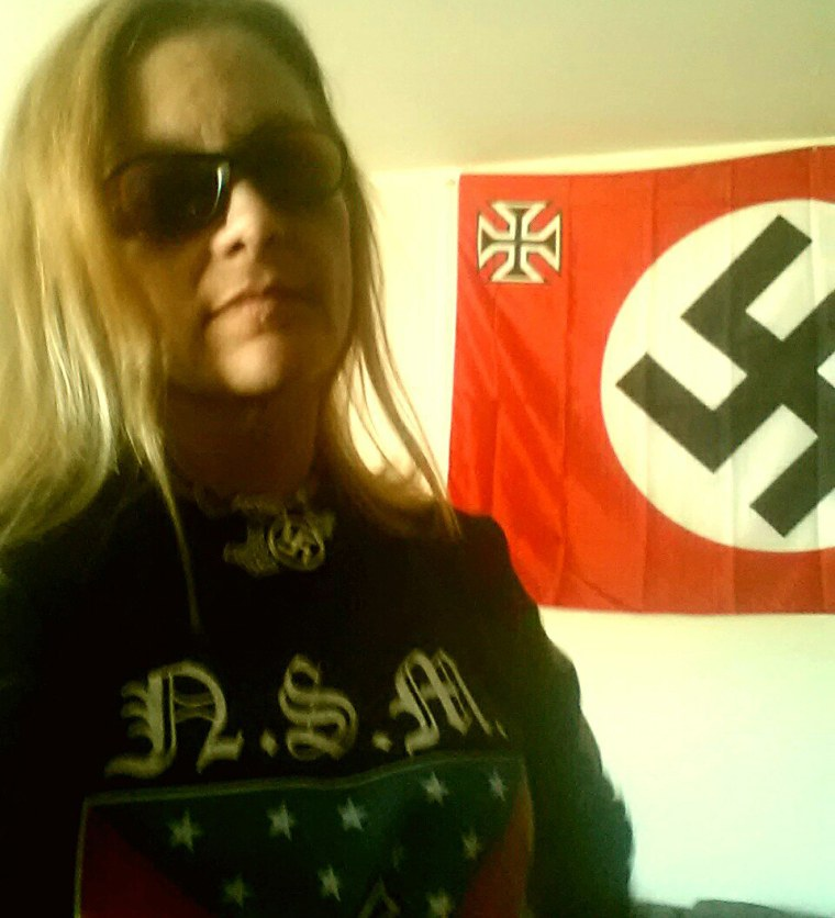 Rebecca Barnette stands in front of a flag with a swastika in her profile picture on the Russian social media site VK.com.