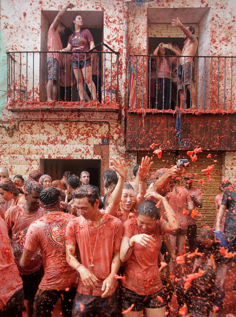 Image: Revellers battle with tomato pulp during the annual 'Tomatina' festival in Bunol near Valencia