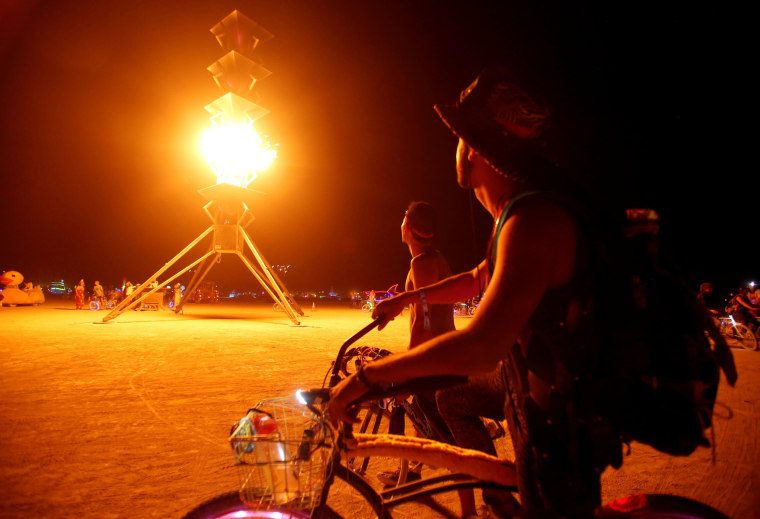 Image: Participants watch the flames on the Spire of Fire at Burning Man