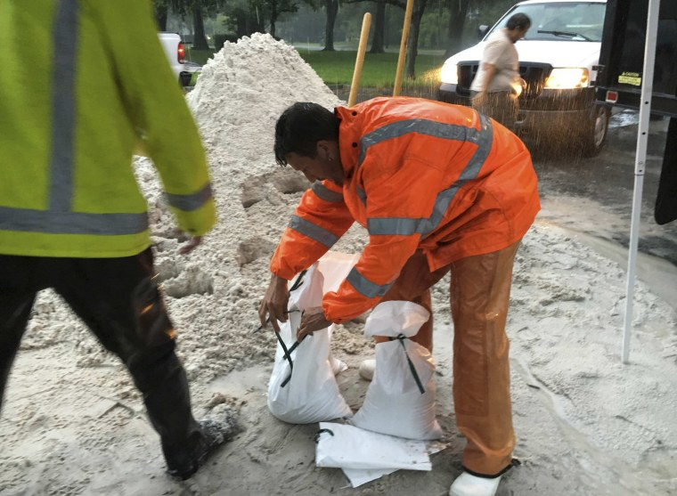 Image: A city worker fills sandbags to help residents prepare for an expected tropical storm in Gulfport