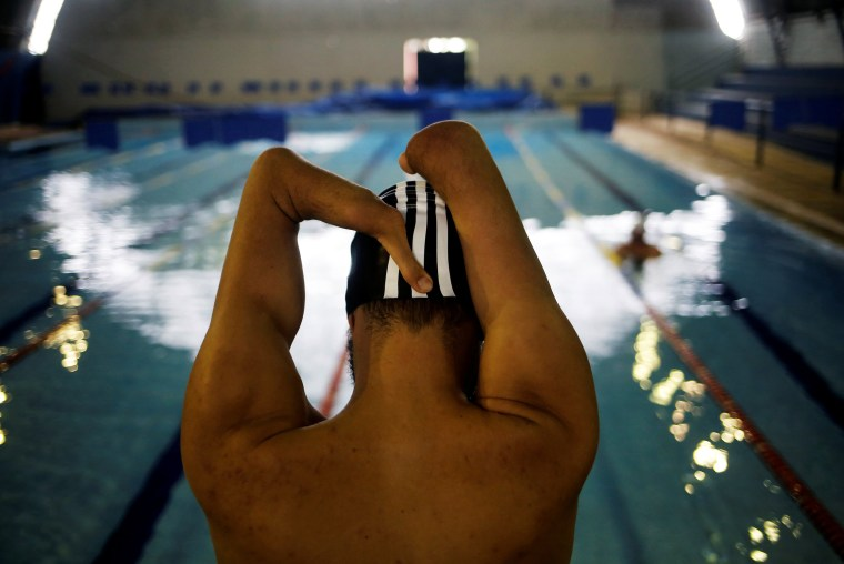Image: Brazil's Paralympic swimmer Daniel Dias stretches during a training session at an indoor swimming pool in Braganca Paulista