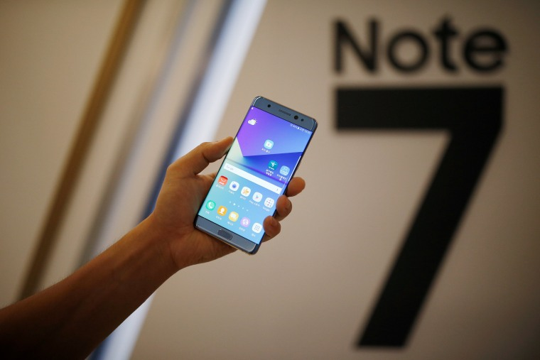 Image: A model poses for photographs with a Galaxy Note 7