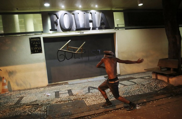 Image: A demonstrator attacks the Folha de S. Paulo newspaper office during a protest against Brazil's new President Michel Temer after Brazil's Senate removed former President Dilma Rousseff in Sao Paulo