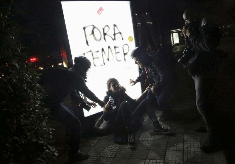 Image: Photographers help a woman who was affected by tear gas during a protest against Brazil's new President Michel Temer after Brazil's Senate removed former Dilma Rousseff in Sao Paulo