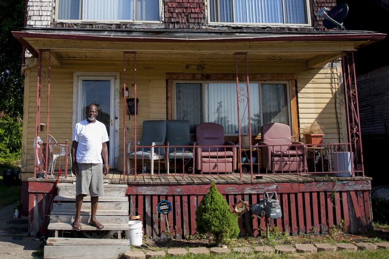 Richard Cooper stands on his front porch in Highland Park, Michigan, across from an empty lot where his elementary school once stood.