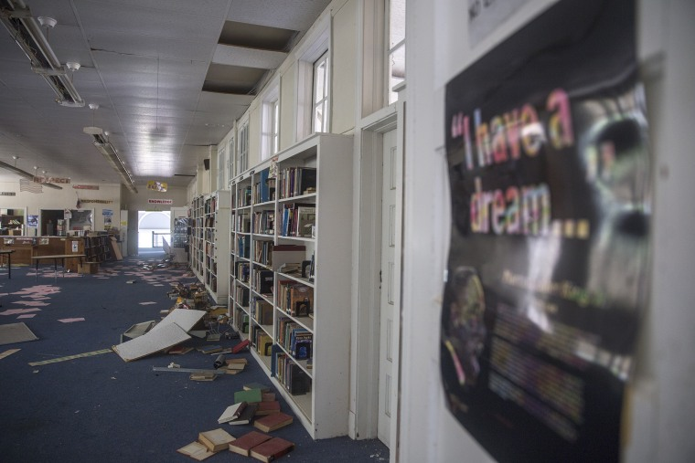 Books are strewn across the floor in the library of the now-closed Drew High School in Mississippi.
