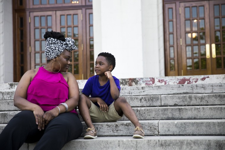 Isis Pettway and her son Caleb sit on the steps of historic Little Rock Central High School, one of the 48 Little Rock schools that Arkansas took control of in 2015. Pettway graduated from the school in 2000 and now sends her 7-year-old son to one of the city'??s elementary schools.