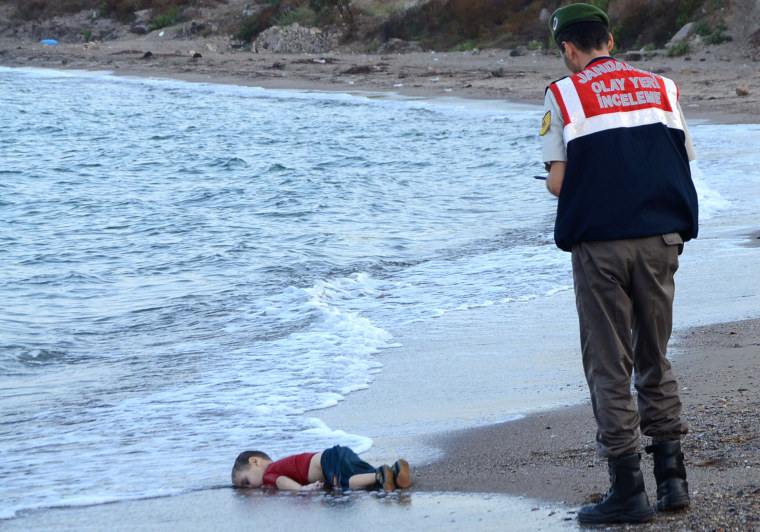 Image: A Turkish police officer stands next to a migrant child's dead body