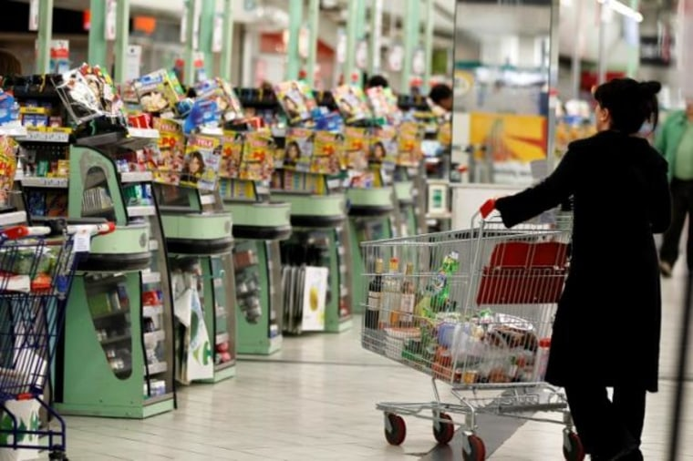 A shopper pushes a shopping trolley down an aisle at a supermarket in Charenton near Paris