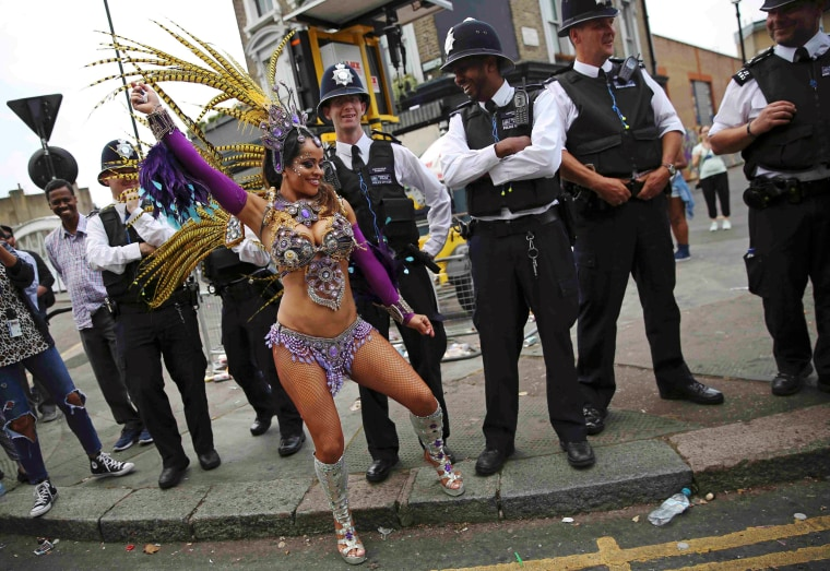 Image: Police look as a performer dances during the Notting Hill Carnival in London