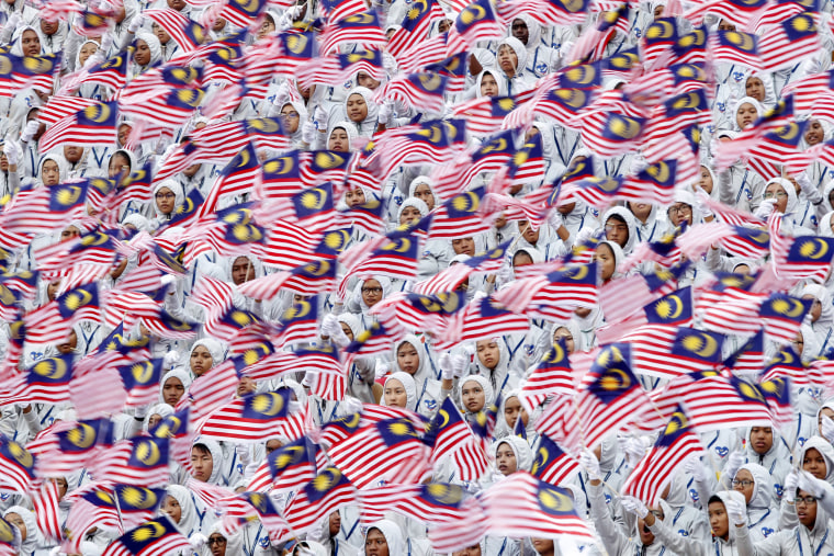 Image: Students wave the Malaysian flag during the 59th National Day celebrations at the Independence Square