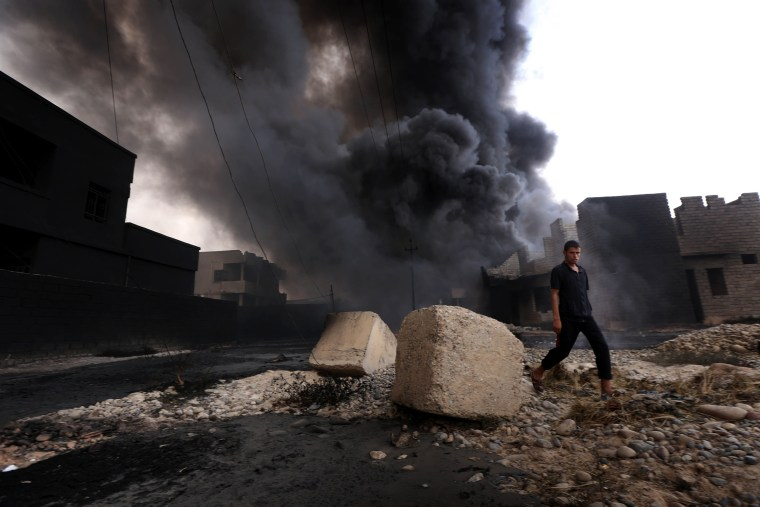 Image: An Iraqi man walks near smoke billowing from oil wells set ablaze by ISIS militants