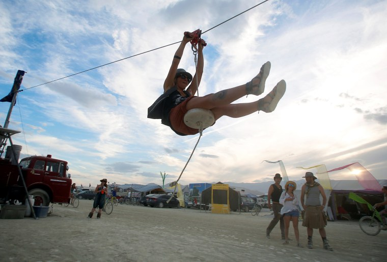 Image: A participant rides a zip line as approximately 70,000 people from all over the world gather for the 30th annual Burning Man arts and music festival in the Black Rock Desert of Nevada, U.S.