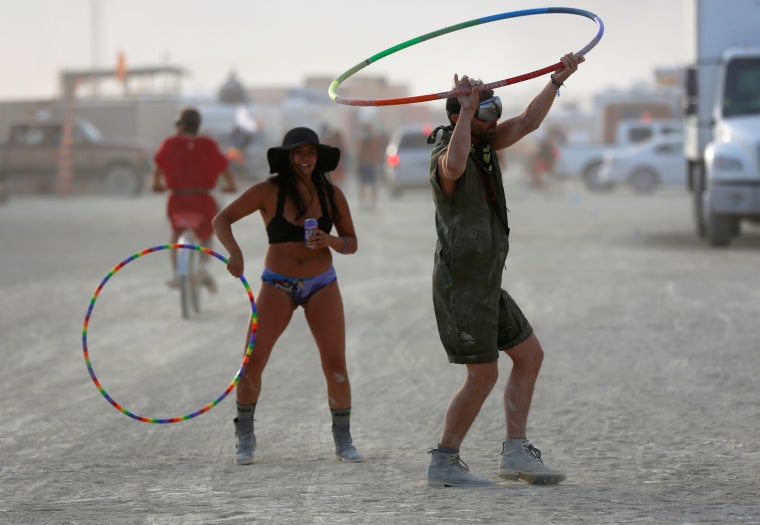 Image: Participants hula-hoop as approximately 70,000 people from all over the world gather for the 30th annual Burning Man arts and music festival in the Black Rock Desert of Nevada, U.S.