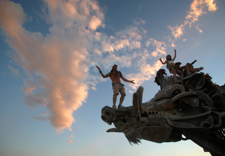 Image: Participants dance and climb on an art installation as approximately 70,000 people from all over the world gather for the 30th annual Burning Man arts and music festival in the Black Rock Desert of Nevada, U.S.