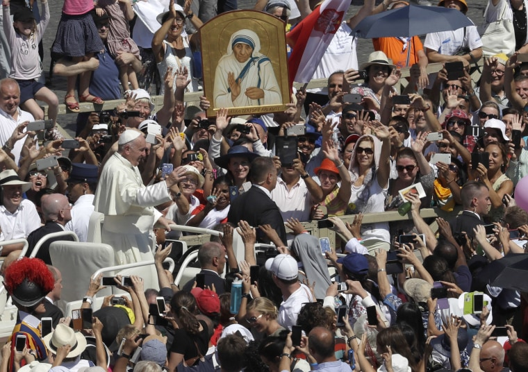Image: Pope Francis passes in front of a portrait of Mother Teresa