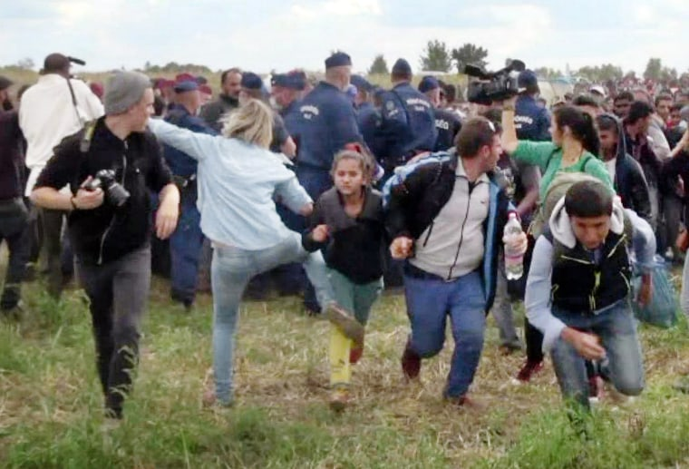 Image: A Hungarian TV camerawoman kicking a child as she runs with other migrants