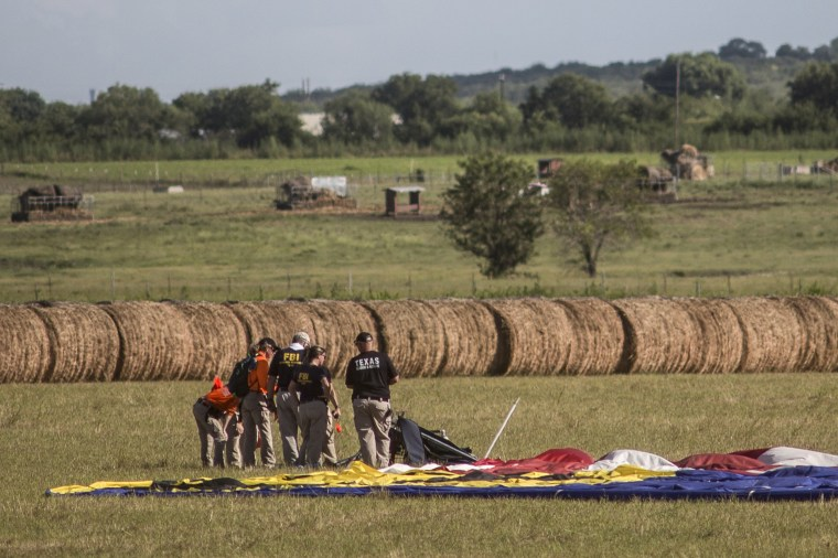 Image: Police and National Transportation Safety Board officials head to a briefing near the site where a hot air balloon crashed west of Lockhart, Texas.
