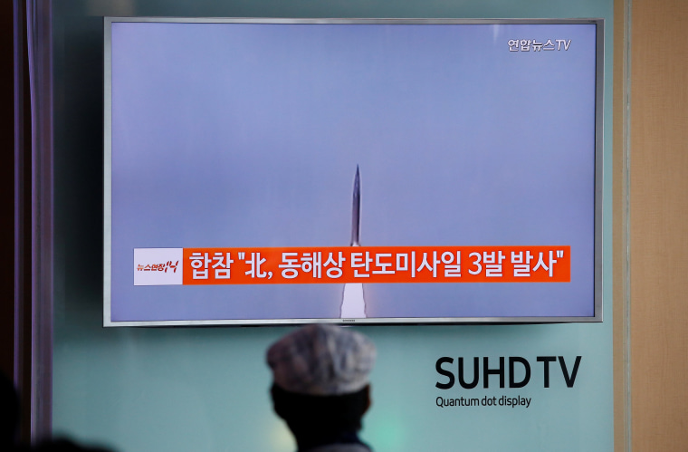 Image: A passenger watches a TV screen broadcasting a news report on North Korea firing three ballistic missiles