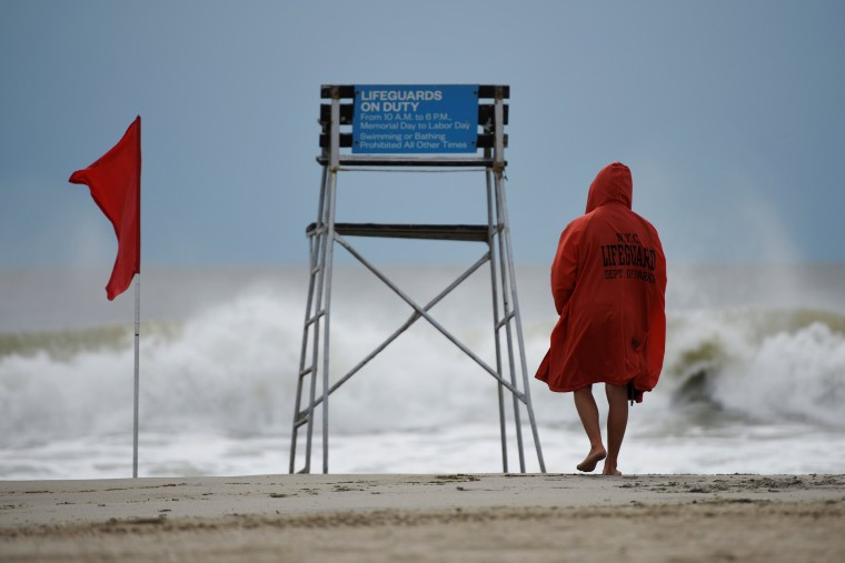 Image: A lifeguard surveys the water where surfers took advantage of the waves at Rockaway Beach in Queens