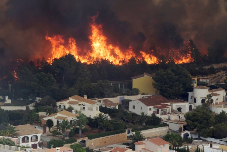 Image: Flames of a wildfire engulf a hillside next to houses in Benitatxell near Alicante