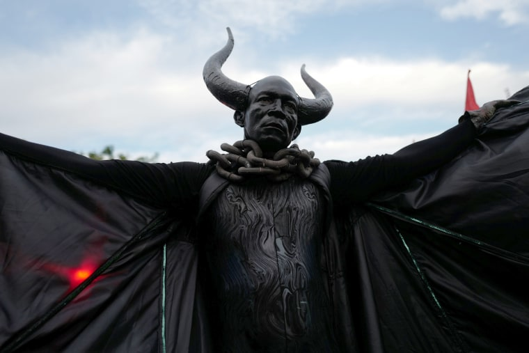 """Image: A man dressed as the """"Bat King"""" walks down the street as he takes part in J'Ouvert in Brooklyn"""