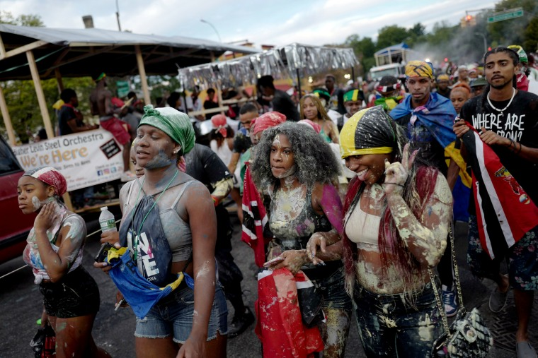 Image: A woman gestures at friends while marching in J'Ouvert, ahead of the annual West Indian-American Carnival Day Parade in Brooklyn