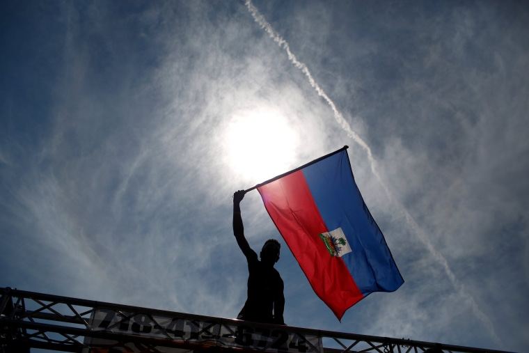 Image: A participant waves a flag during the West Indian Day Parade in the Brooklyn borough of New York