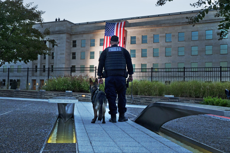 Standing at the Pentagon Memorial, a K-9 officer pauses as he looks toward the U.S. flag as it is draped on the side of the Pentagon where the building was attacked, on Sept. 11, 2015, the 14th anniversary of the attack.