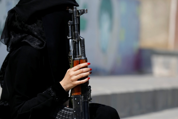 Image: Woman loyal to the Houthi movement holds a rifle as she takes part in a parade to show support to the movement in Sanaa, Yemen