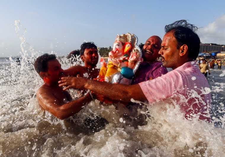 Image: Devotees carry an idol of the Hindu god Ganesh, the deity of prosperity, into the Arabian Sea on the second day of Ganesh Chaturthi festival in in Mumbai
