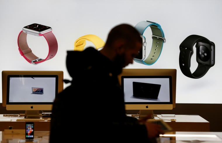 Image: Customer walks past screen displaying advertisement of Apple iWatch in store of Russia's biggest electrical and white goods retailer