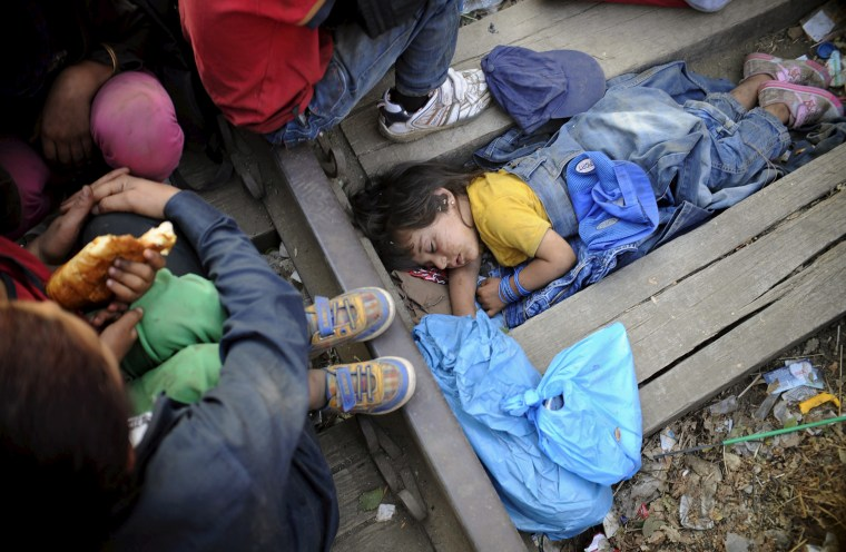 Image: Rashida, part of a new group of immigrants, sleeps as they wait at border line of Macedonia and Greece to enter into Macedonia near Gevgelija railway station