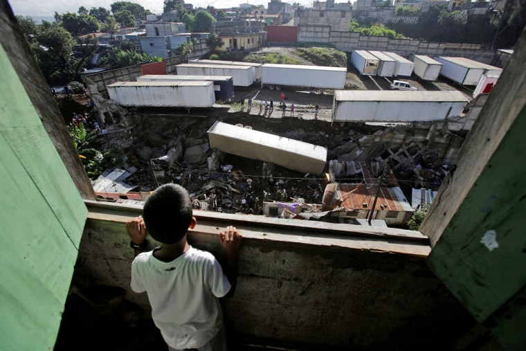 Image: Child looks at the site where a landslide took place causing a trailer to fall on top of homes causing several casualties in Villanueva