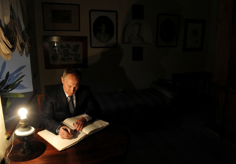 Image: Russian President Putin signs a visitors' book at Russian writer Leo Tolstoy estate museum in Yasnaya Polyana outside Tula