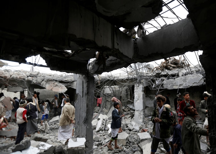 Image: People gather at a building destroyed by Saudi-led air strikes in the northwestern city of Amran, Yemen