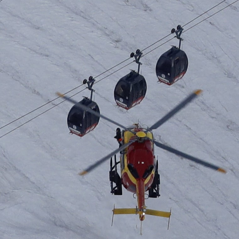 Image: An EC-135 helicopter operated by the French Societe' Civile hovers near three cars of the Panoramic Mont Blanc cable car that stalled