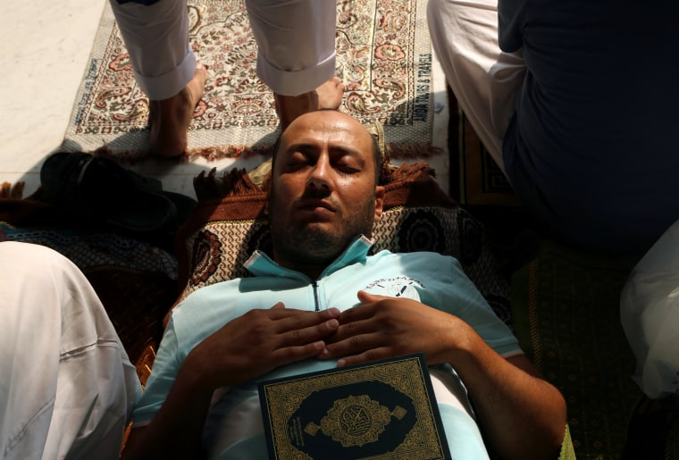 Image: A Muslim pilgrim sleeps while reading the Koran at the Grand mosque in Mecca