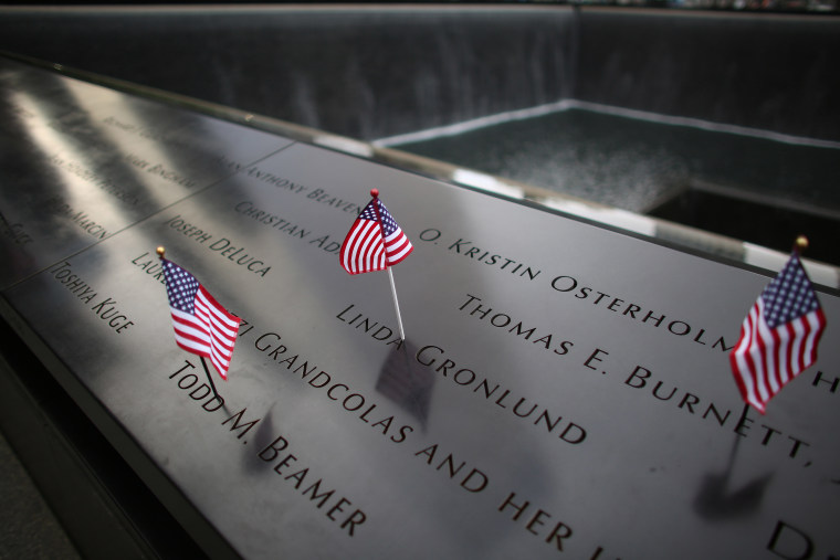 American flags are placed on inscribed names along the edge of the South Tower Memorial during memorial observances on the 13th anniversary of the Sept. 11 terror attacks on the World Trade Center in New York, Thursday, Sept. 11, 2014.