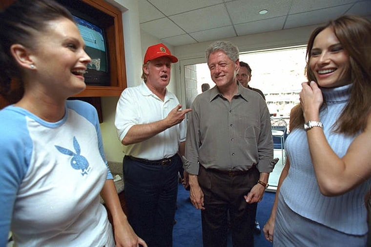 President Bill Clinton talks with Donald Trump, as Melania Knauss, right, Trump's future wife, and an unidentified woman look on at the U.S. Open Tennis Championship match in New York on on Sept. 8, 2000.