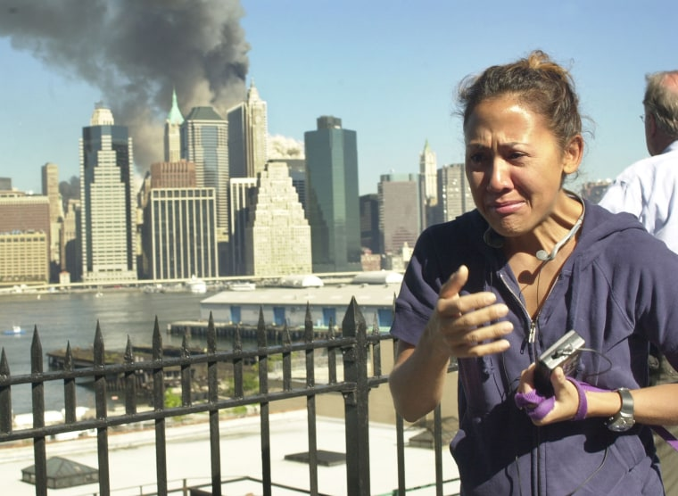A woman reacts to a third explosion, possibly the collapse of the World Trade Center towers, while observing from the Brooklyn Promenade, which provides a view of the Manhattan skyline, Sept. 11, 2001, in New York.