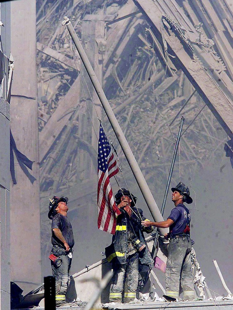 Firefighters raise a flag at the World Trade Center as work at the site continues after hijackers crashed two airliners into the center.
