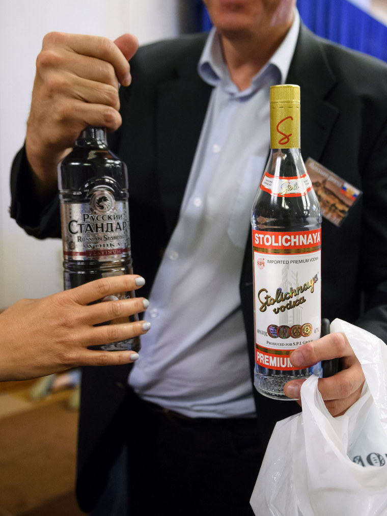 Image: A reporter holds vodka delivered to waiting journalists by Russia's foreign minister Lavov after meetings went late into the evening.