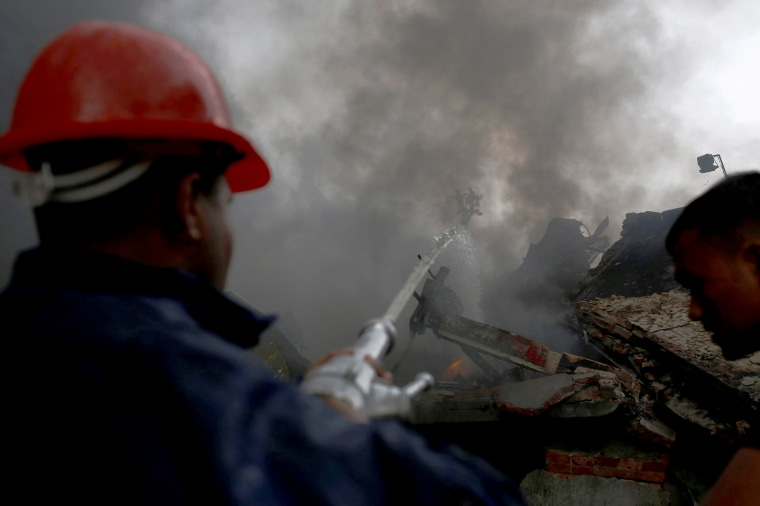 Image: Firefighters extinguish a fire at a garment packaging factory outside Dhaka