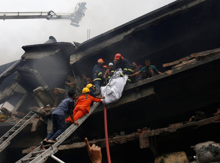 Image: Firefighters remove a dead body at a food and cigarette packaging factory after fire broke out outside of Dhaka  Dhaka