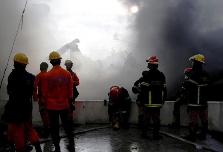 Image: Firefighters stand at the site of a fire at a packaging factory outside Dhaka