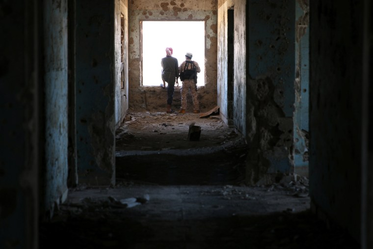 Image: Rebel fighters stand in a damaged building in Quneitra countryside