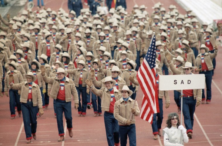 Frank Masley of Newark carries the flag as members of the U.S. Olympic team march in opening ceremony at Kosevo Stadium in Sarajevo, on Feb. 8, 1984 for the XIV winter Olympic Games. The placard marked sad is the Yugoslav designation for USA.