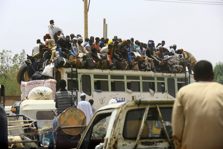 Image: People ride on a bus as they return to their families ahead of the Eid al-Adha festival in Khartoum