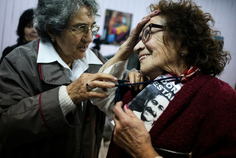 """In this Sept. 5, 2016 photo, Violeta Zuniga, 83, left, and Martha Perez, 80, talk after a performance of """"Cueca Sola"""" at a school in Santiago, Chile."""